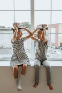 one boy and one girl holding books on head to display page for adhd counseling