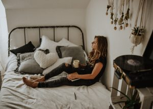 Counseling for OCD image woman on bed with coffee looking outside
